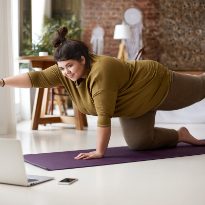 Woman doing yoga in front of laptop